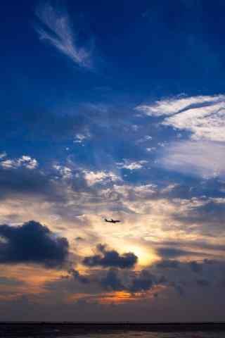 夕阳下空中的飞机唯美手机壁纸