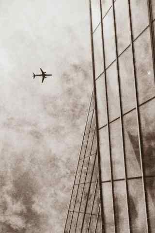 飞过高楼上空的飞机文艺清新手机壁纸