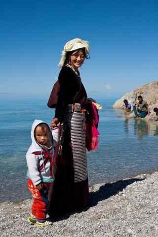 纳木错湖边散步的藏区妇女图片手机壁纸