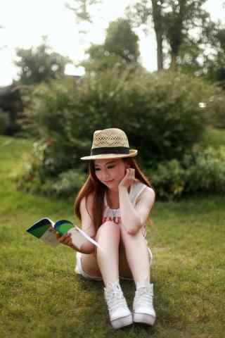 坐在草地上看书的女孩壁纸
