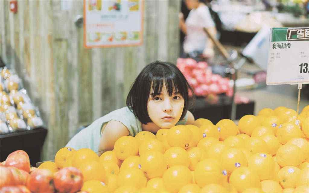 橙子堆里的短发美女图片壁纸
