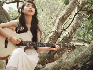 少女在树上弹奏吉